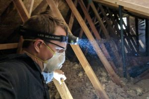 handyman performs residential property maintenance in attic of sacramento home